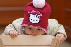 Baby girl biting chair Stock Photos