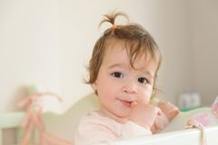 Baby Girl Biting Her Forefinger In Bed Stock Image
