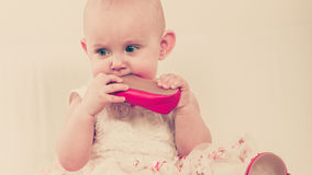Baby girl biting shoe Royalty Free Stock Photo