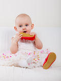 Baby girl biting shoe Stock Image