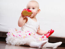 Baby girl biting shoe Stock Images