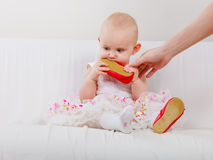 Baby girl biting shoe. Infant in time of teething. Sweet cute baby girl biting chewing red shoe. Young adorable child wearing white princess dress Royalty Free Stock Photos