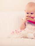 Baby girl biting shoe. Infant in time of teething. Sweet cute baby girl biting chewing red shoe. Young adorable child wearing white princess dress Stock Image