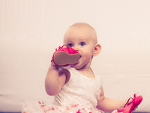 Baby girl biting shoe. Infant in time of teething. Sweet cute baby girl biting chewing red shoe. Young adorable child wearing white princess dress Royalty Free Stock Photography