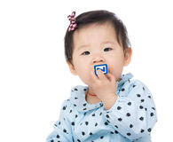 Baby girl biting toy block Stock Images