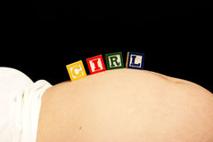 Baby Girl Blocks. An expecting mother rests some baby blocks on her pregnant belly that spell out the word girl Royalty Free Stock Photography