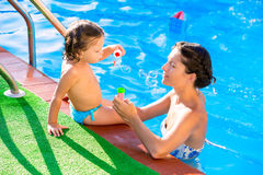 Baby girl blowing soap ballons with mother in pool Stock Image