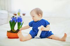 Baby girl in blue dress sitting on bed with blue hyacinths royalty free stock photography