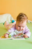 Baby girl with book. Cute baby girl lying on bed with open book and teddy Stock Image