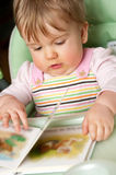 Baby girl with book. Cute baby girl with opened children book Royalty Free Stock Photo