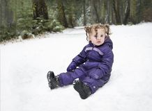 Little girl in sitting purple snow suit royalty free stock photos