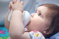 Baby girl with bottle. Nine months old baby drinking milk from bottle holding with both hands Royalty Free Stock Images