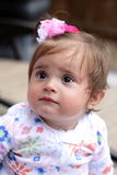 Baby girl with a bow in her hair. A 1 yr old baby girl with a pink bow in her dark hair looking up questioningly.  Shallow depth of field. Selective focus Stock Images