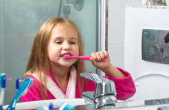 Baby Girl Brushing Her Teeth in the Morning at Bathroom Royalty Free Stock Image