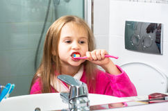 Baby Girl Brushing Her Teeth in the Morning at Bathroom Stock Photo