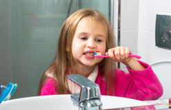 Baby Girl Brushing Her Teeth in the Morning at Bathroom Stock Images