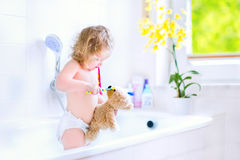 Baby girl brushing teeth playing with a teddy bear. Happy funny baby girl wearing a diaper brushing her teeth and playing with her teddy bear toy and a stock image