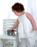 Baby Girl with Bunny. Baby girl standing in front of white background with gray bunny on bench Stock Image