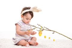 Baby girl with bunny ears. Baby girl in easter bunny costume, playing with easter eggs hanging from willow branch. Isolated on white background Stock Images