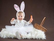 Baby girl with bunny ears. On brown Stock Image