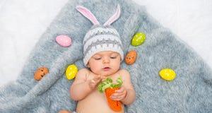 Baby girl in bunny hat lying on gray blanket Stock Photos