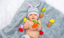 Baby girl in bunny hat lying on gray blanket Royalty Free Stock Photos