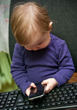 Baby girl call center. Concept. Cute child sit with desktop computer and hold on mobile phone royalty free stock photos
