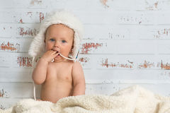 Baby girl in a cap enjoying warmth of the room. Naked baby girl sitting in a warm interior wearing white cap. Rustic wall in the back Stock Photos