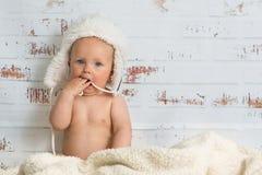 Baby girl in a cap enjoying warmth of the room Stock Photos