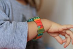 Baby girl carefully looking at colorful smart wrist watches at home. Close up portrait of baby girl carefully looking at colorful smart wrist watches at home royalty free stock photos
