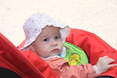 Baby girl in carriage. Baby girl with panama sitting in carriage Royalty Free Stock Images