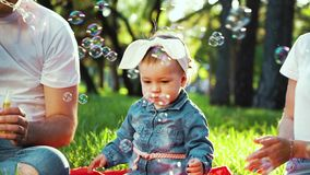 Baby girl catching soap bubbles blown by her father at family picnic in park. Traditional family of three sitting on green grass in sunny park. people, family stock footage