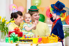 Baby girl celebrating birthday with parents. Baby girl celebrating first birthday with parents and clown Stock Images