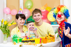 Baby girl celebrating first birthday and clown. Baby girl celebrating first birthday with parents and clown Stock Photos