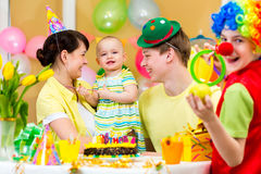 Baby celebrating first birthday with parents and clown. Baby girl celebrating first birthday with parents and clown Royalty Free Stock Photo