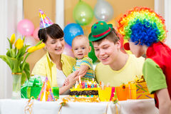Baby girl, parents and clown on birthday. Baby girl celebrating first birthday with parents and clown Stock Photo