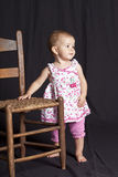 Baby girl and chair Royalty Free Stock Photography