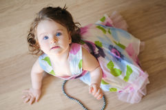 Baby-girl with chaplet. Cute baby-girl well-dressed sits on a floor and plays with chaplet Royalty Free Stock Photo