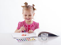 Baby girl child drawing red heart. Happy cheerful baby girl child drawing red heart with brush in album with painting tools laughing isolated on a white stock photo