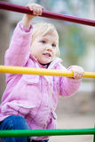 Baby girl on child's playground in spring time. Cute baby girl plays on child's playground, she is climbing on gymnastic stairs Stock Photos