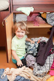 Baby girl at closet. Baby girl chooses dress at closet royalty free stock images