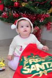 Baby Girl at Christmas. Baby girl opening Christmas Presents by the Xmas tree Stock Photo