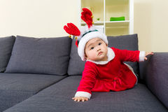 Baby girl with christmas dressing and crawling on sofa Royalty Free Stock Images