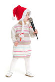Baby girl in Christmas hat singing into microphone Stock Photo