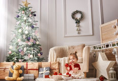Baby girl on Christmas. Merry Christmas and Happy Holidays! Cute little child girl is decorating the Christmas tree indoors royalty free stock image
