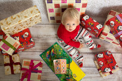 Baby girl among the christmas presents. Dressed festively girl with stacks of present boxes around sitting on the floor and looking at the camera Royalty Free Stock Images