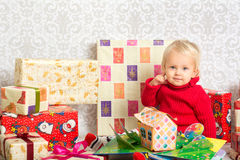 Baby girl among the christmas presents. Dressed festively girl with stacks of present boxes around sitting on the floor and playing with paper gingerbread house Stock Image
