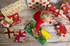 Baby girl among the christmas presents. Dressed festively girl with stacks of present boxes around sitting on the floor and playing with paper gingerbread house Stock Images