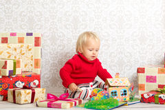Baby girl among the christmas presents. Dressed festively girl with stacks of present boxes around sitting on the floor and playing with paper gingerbread house Stock Photography