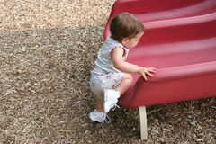 Baby Girl Climbing. Baby girl trying to climb on red slide at playground. Shot with a Canon 20D Royalty Free Stock Image